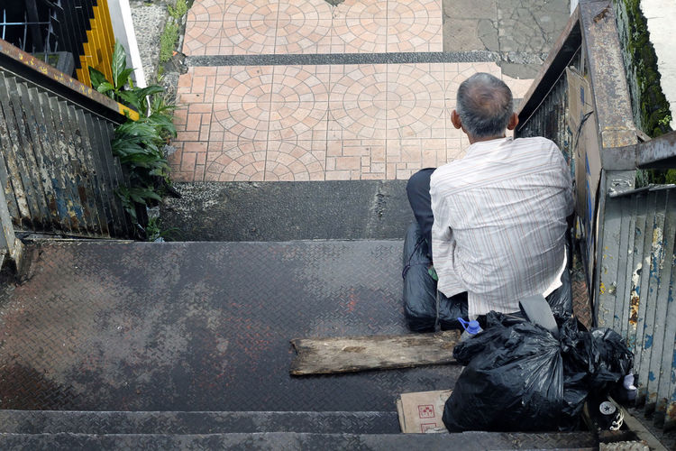 Rear view of man sitting on steps in city