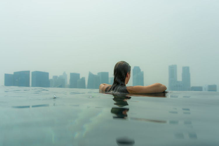 Rear View Of Woman In Infinity Pool Against Skyscrapers