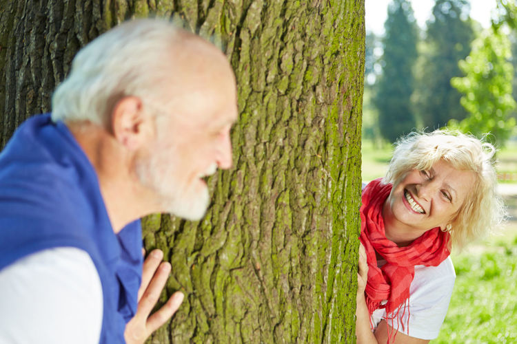 Cheerful Senior Couple Standing By Tree Trunk At Park