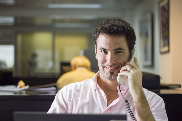 Portrait Of Smiling Man Talking On Telephone In Office