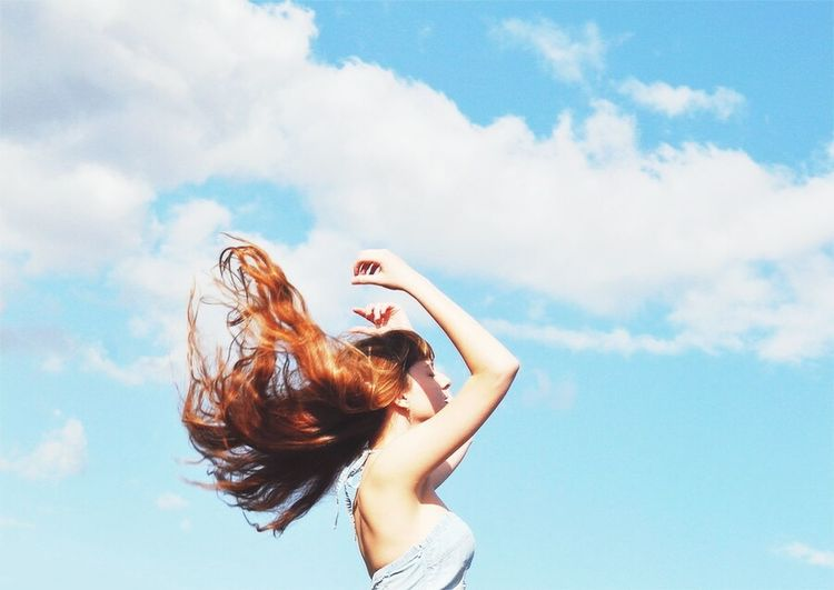 Low angle view of woman standing against cloudy sky