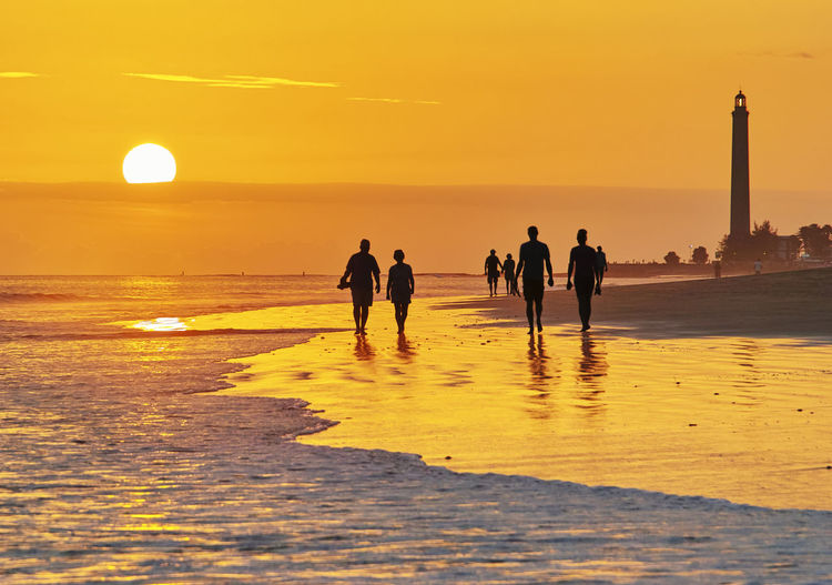 Silhouette People Walking At Beach Against Orange Sky During Sunset