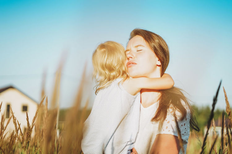 Young woman mom with baby girl on hands hug in backyard of cottage in sunset light