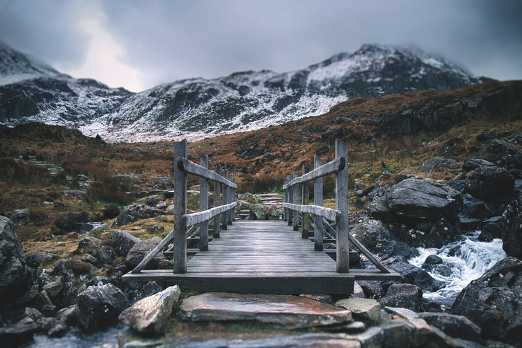 Footbridge over lake against mountains during winter