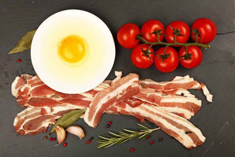 High angle view of bacon with cherry tomatoes and egg on slate