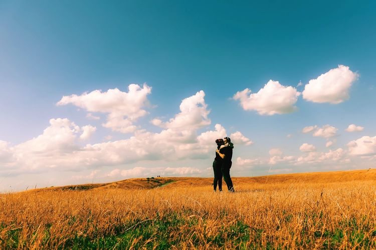 Couple Kissing On Grassy Field Against Sky During Sunny Day
