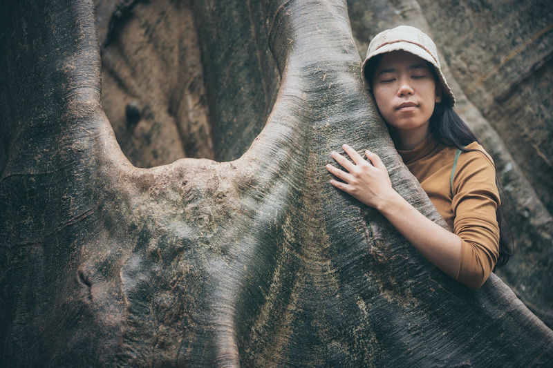 Woman embracing tree trunk
