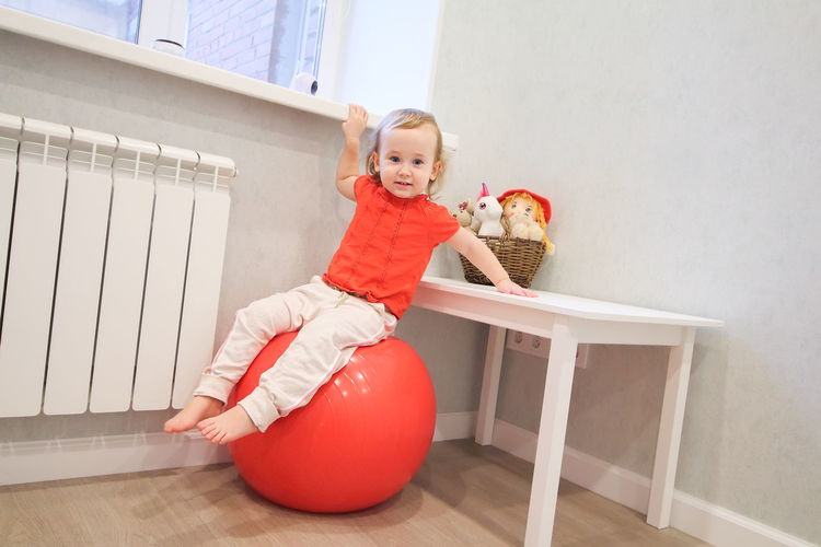 Portrait of smiling girl sitting at fitness ball at home
