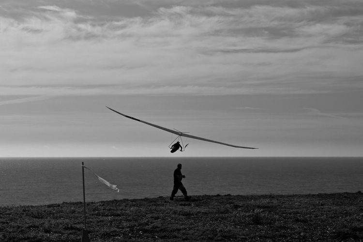 Side view of man walking by hang glider flying above sea