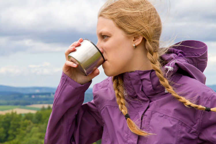 Close-up of woman drinking water from bottle cap against sky
