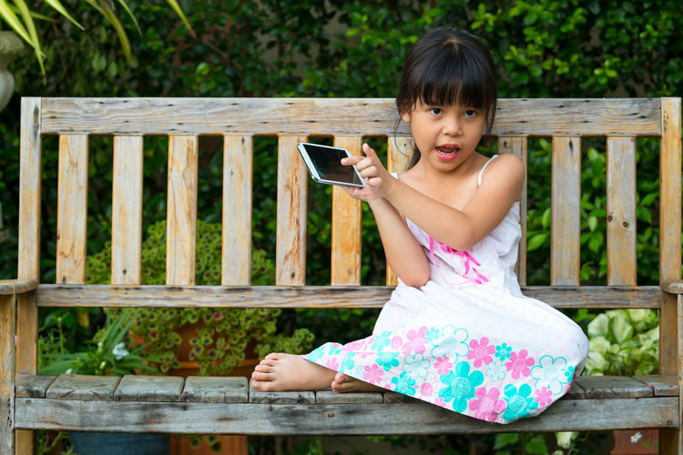 Portrait of girl holding mobile phone while sitting on wood