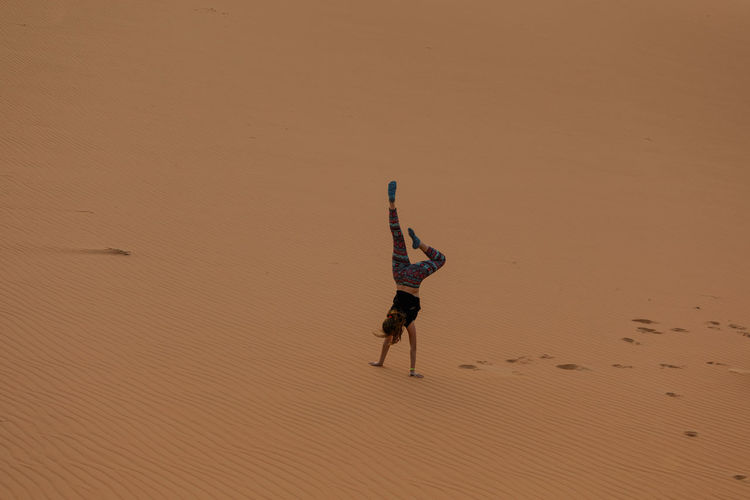 Dancing in the desert, Abu Dhabi, UAE Desert Deserts Around The World Arid Climate Arms Raised Beach Beauty In Nature Climate Day Desert Full Length Handstand  Human Arm Land Leisure Activity Lifestyles Men Nature One Person Real People Sand Scenics - Nature Sunlight Trip Urban Skyline Vacations