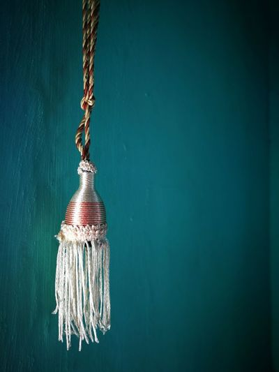 Close-up of tassel hanging against wall