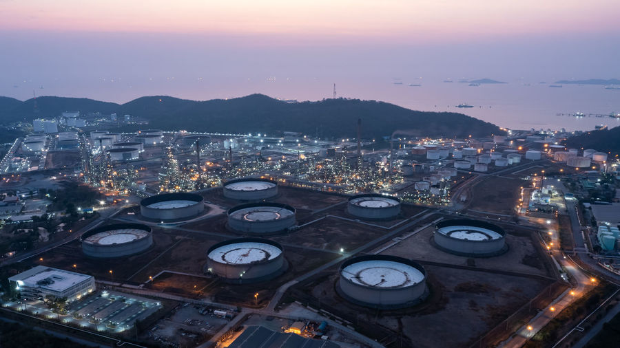 Aerial view industry factory oil and gas chemical tank and oil refinery and mountain at twilight