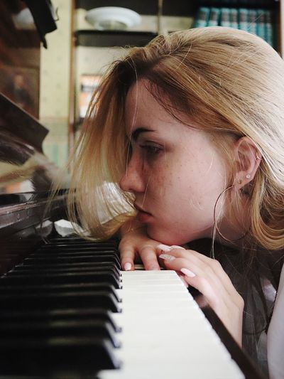 Close-up of teenage girl leaning on piano keys