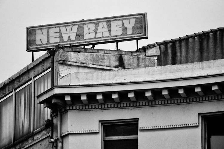 Baby New Wall Writing Writing On The Walls Architecture Building Building Exterior Built Structure Contrast Low Angle View New Baby No People Old Old Buildings Old Sign Saying New Run Down Sign Text Wall - Building Feature