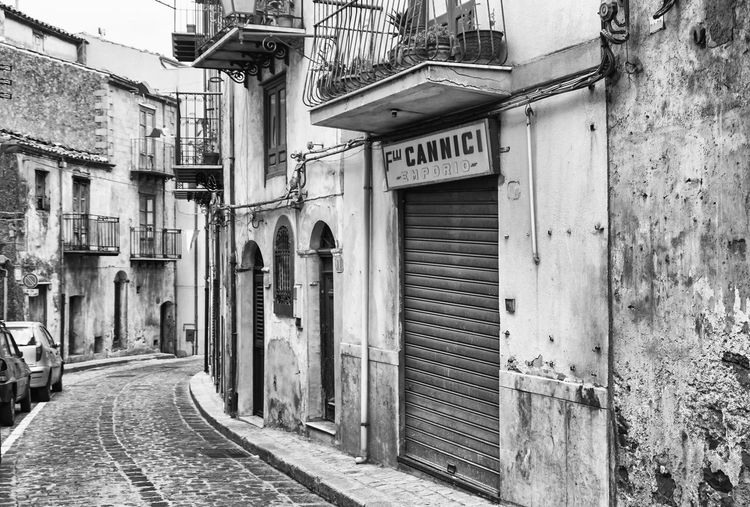 store in an old town, Sicily, Italy Entrance Street City Door No People Alley Text Closed Black And White Sicily Store Old Old Town Cannici