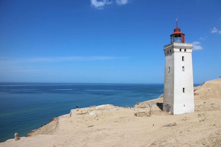 LIGHTHOUSE ON BEACH AGAINST BLUE SKY