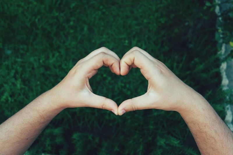 Cropped hands of man making heart shape over field