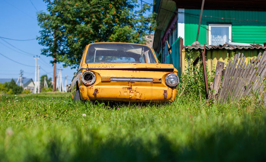 Old yellow wrecked car in vintage style. abandoned rusty yellow car.