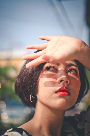 Woman looking away while shielding eyes in city
