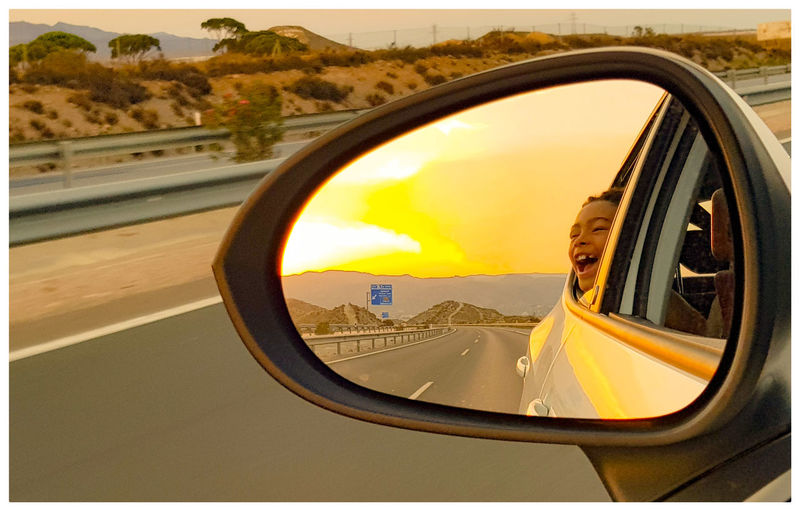 Happy Boy Screaming Through Car Window Seen In Side-View Mirror During Sunset