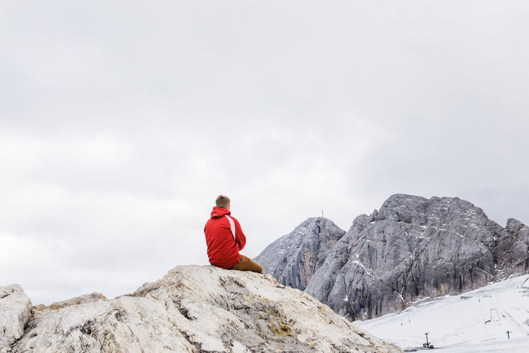 Person on rock by snowcapped mountain against sky