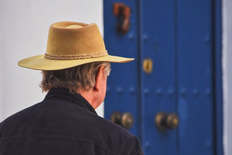Close-up of man wearing hat against door