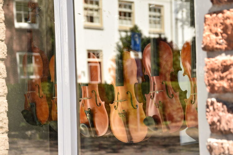 Architecture Arts Culture And Entertainment Building Exterior Day Fashion Focus On Foreground For Sale Glass - Material Music No People Outdoors Reflection Retail  Retail Display Shoe Shopping Store Store Window Transparent Violin Violin Store Window