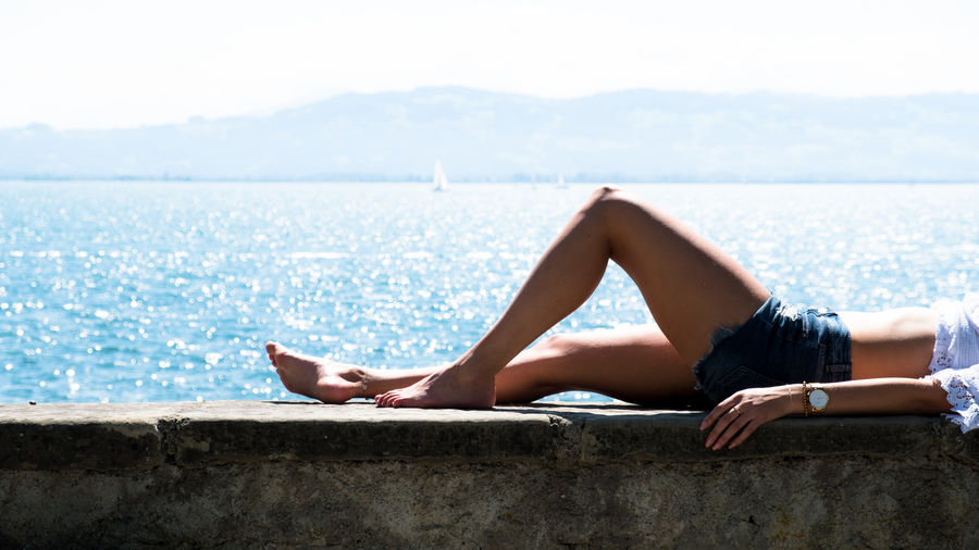 Low Section Of Woman Relaxing On Retaining Wall By Sea