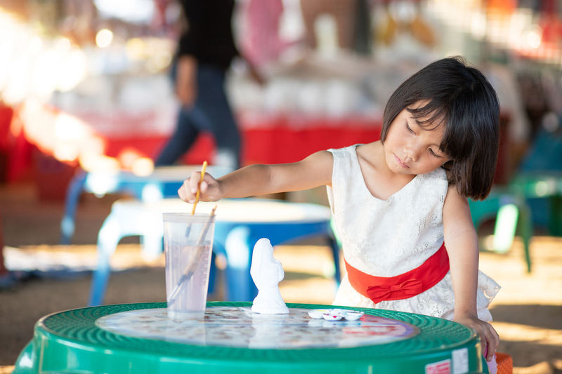 Girl with art and craft equipment on table