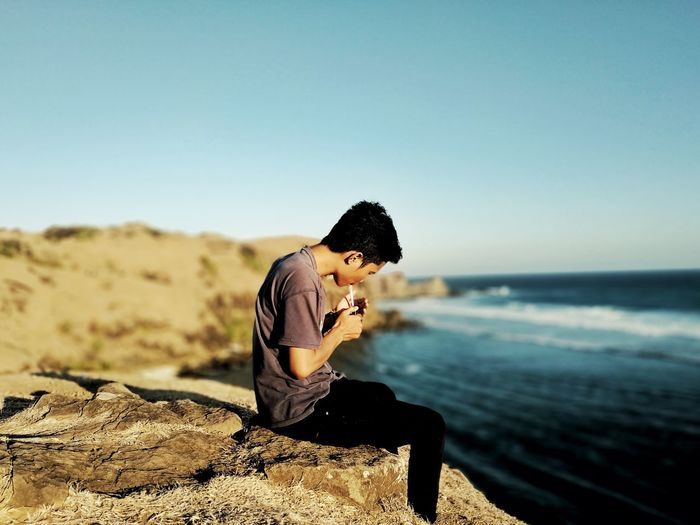 Side view of young man smoking cigarette while sitting on rock by sea against clear sky