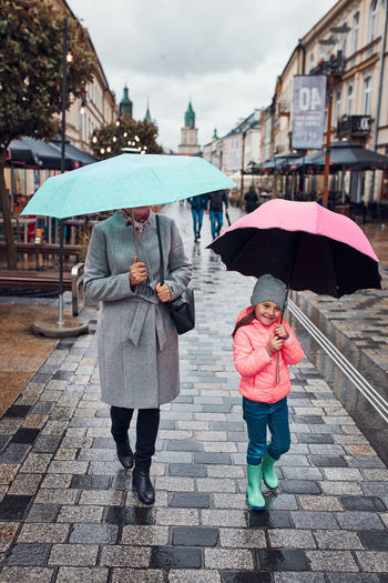 Mother and her little daughter holding the pink and blue umbrellas walking in a downtown