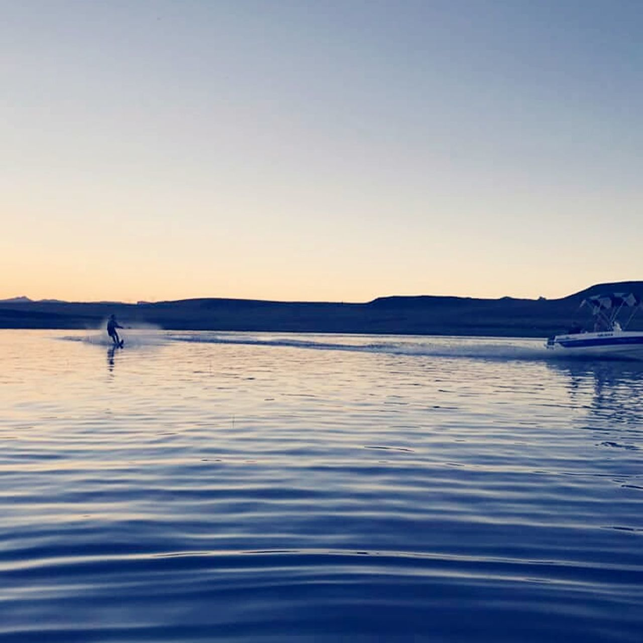 water, nature, clear sky, tranquility, beauty in nature, scenics, sunset, waterfront, outdoors, rippled, tranquil scene, lake, blue, nautical vessel, sky, mountain, transportation, no people, vacations, travel destinations, sailing, day, paddleboarding