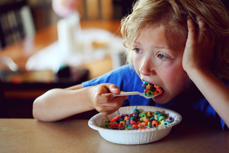 Close-up of thoughtful boy eating multi colored breakfast cereals on table