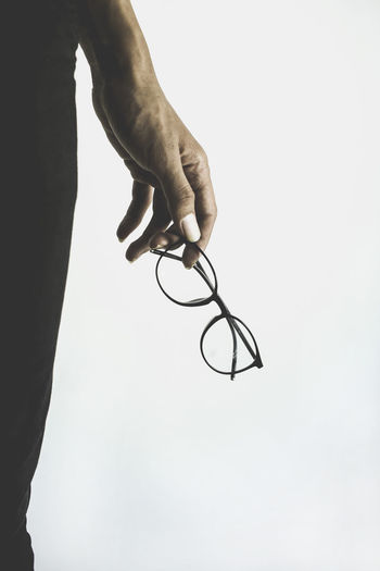 Close-up of hand holding eyeglasses against white background