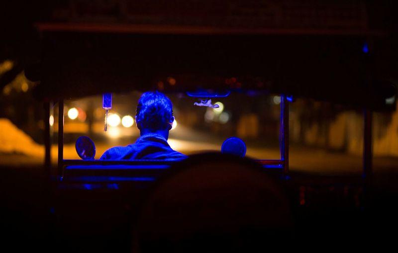 Rear view of driver in illuminated jinrikisha at night