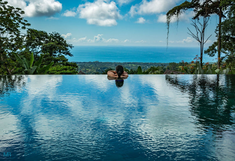 Rear view of woman in infinity pool