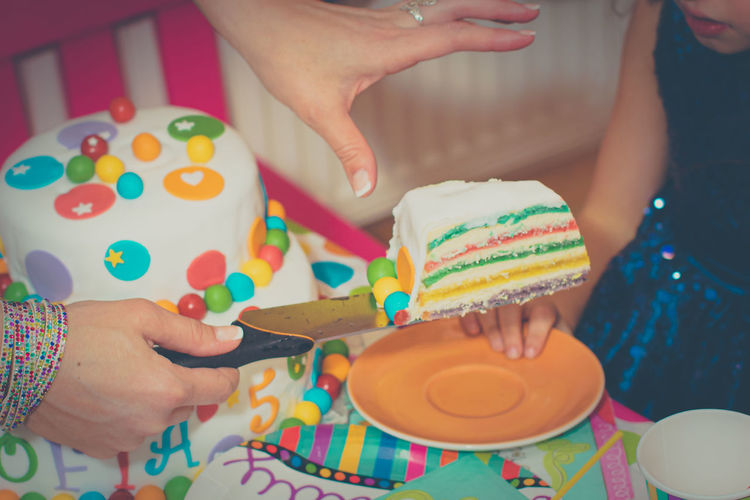 Midsection of woman holding multi colored cake