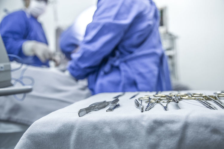 Midsection of surgeons operating patient by surgical equipment in hospital