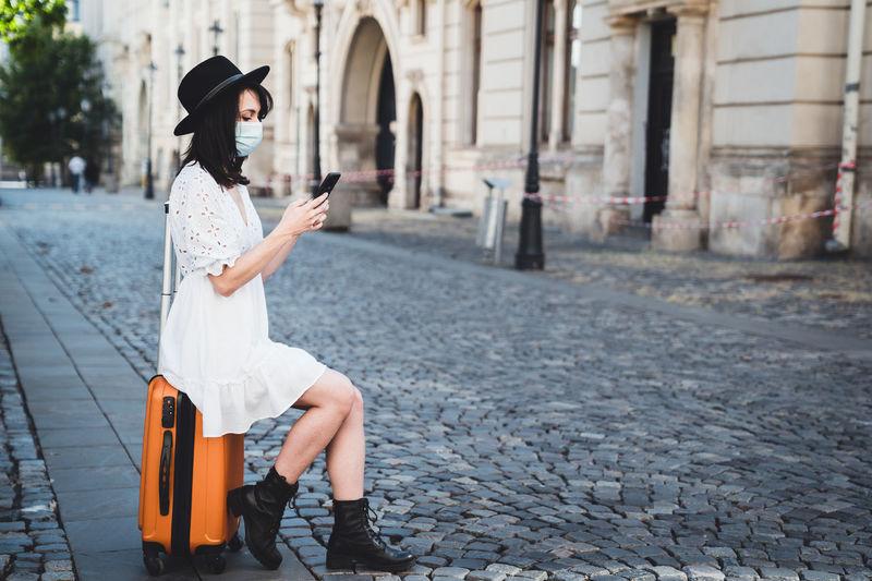 Full length of woman sitting on street