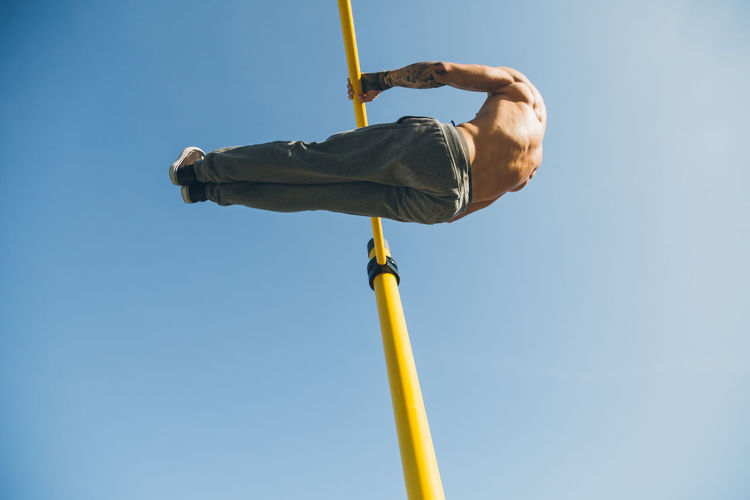 Rear view of man hanging on bar against sky