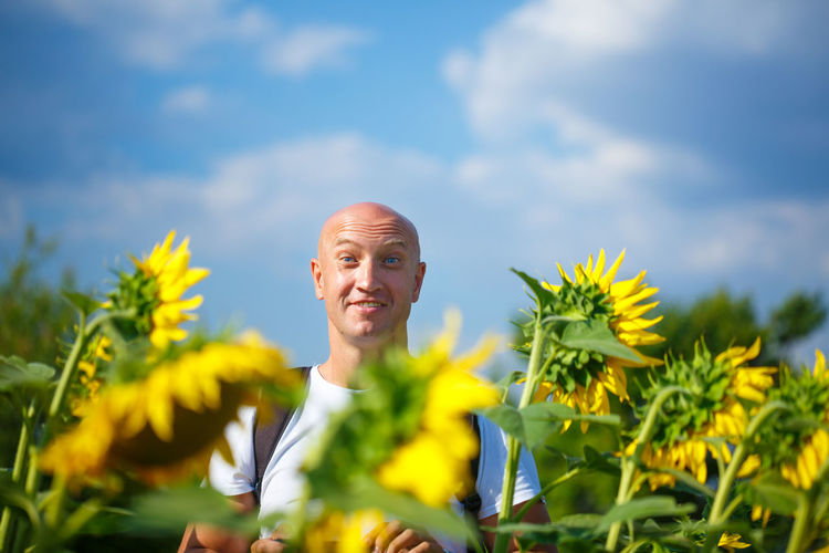 A cheerful bald man in a field of blooming yellow sunflowers against a blue sky stands smiling