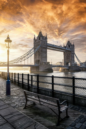 The iconic Tower Bridge in London, UK, during a cloudy sunrise Architecture Sky Cloud - Sky Bridge City Sunset Travel Destinations River Water Travel Outdoors Tourism Building Exterior Built Structure London Sunrise Tower Bridge  Landmark Tourist Attraction  Thames River Sightseeing Morning Sunlight Bench Riverside
