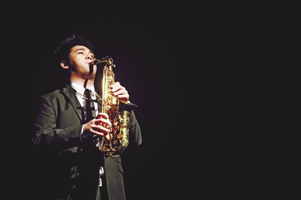 music, musical instrument, musician, saxophone, playing, black background, holding, men, one person, arts culture and entertainment, performance, wind instrument, real people, standing, lifestyles, skill, young adult, jazz music, outdoors, one man only, adult, day, people, adults only