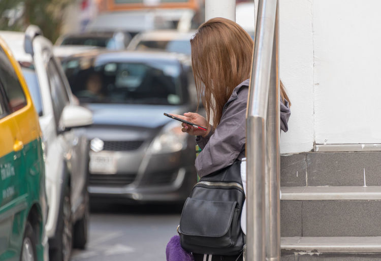 Side View Of Woman Using Phone While Standing At Bus Stop