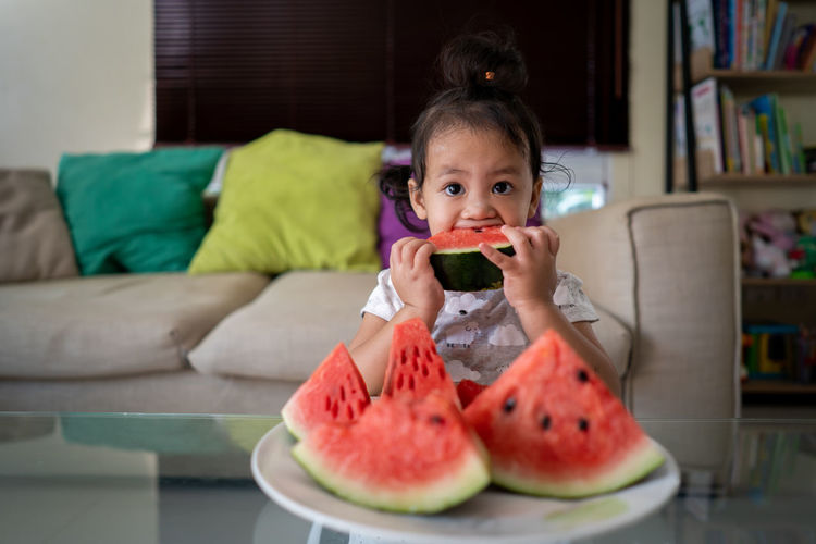 Portrait of boy holding watermelon at home