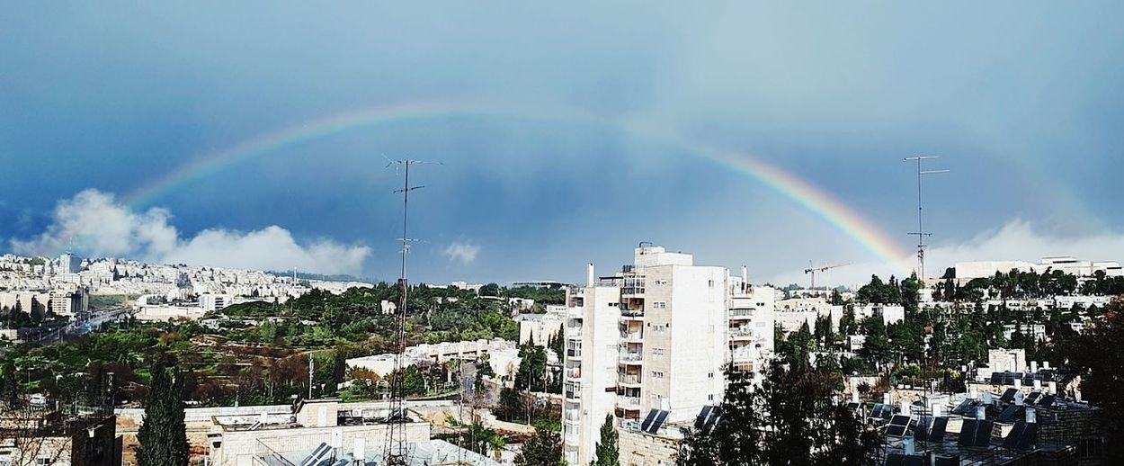 Panoramic view of rainbow over buildings in city