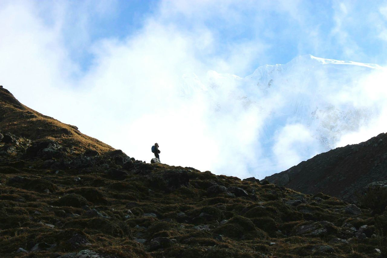 mountain, one person, sky, cloud - sky, leisure activity, real people, nature, adventure, low angle view, hiking, beauty in nature, day, standing, men, outdoors, lifestyles, landscape, full length, scenics, one man only, people