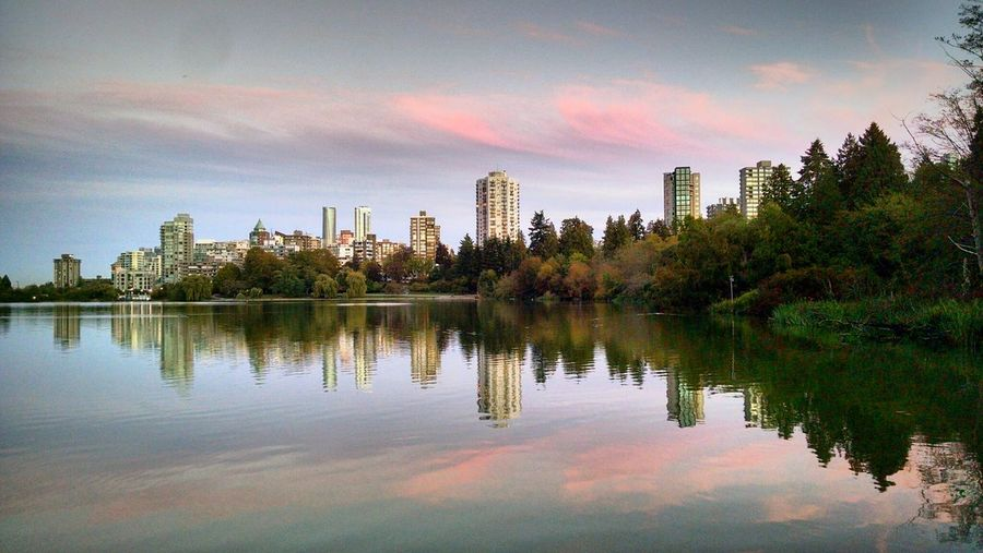 Scenic view of lake by cityscape against sky during sunset